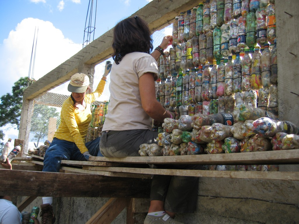 Volunteers building bottle wall